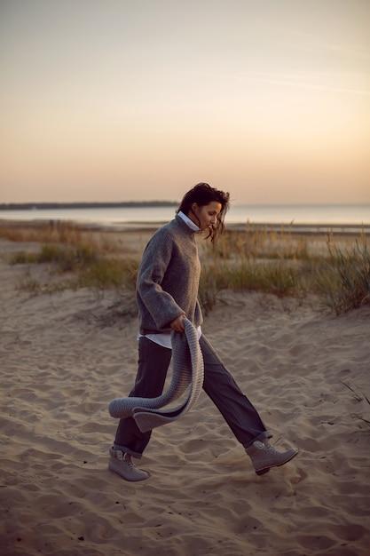 Kobieta W Szarym Swetrze I Spodniach Przychodzi Z Szalikiem Na Plaży W Butach O Zachodzie Słońca Przy Trawie Premium Zdjęcia