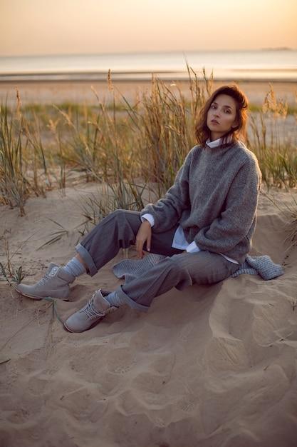 Kobieta W Szarym Swetrze I Spodniach Siedzi Na Plaży W Butach O Zachodzie Słońca Przy Trawie Premium Zdjęcia