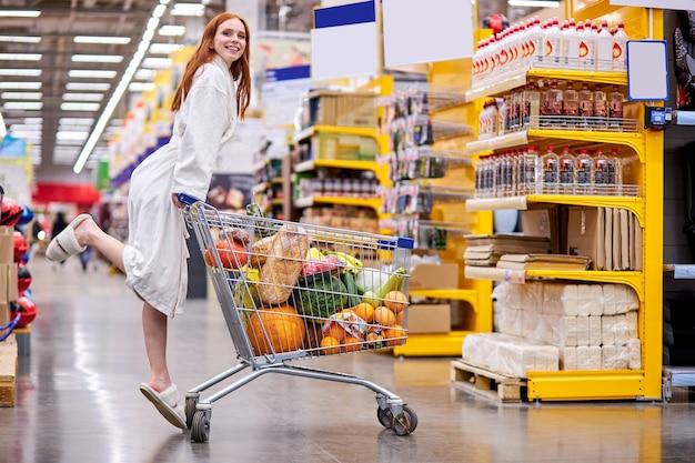 Kobieta W Szlafroku Korzystających Z Zakupów W Supermarkecie, Niosąc Wózek Pełen Jedzenia, W Sklepie Spożywczym, Uśmiech Premium Zdjęcia