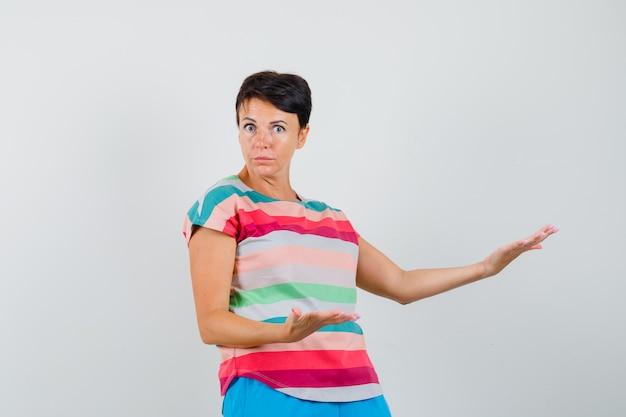 Kobieta W T-shircie W Paski, Pokazująca Coś Lub Witająca I Wyglądająca Na Zdziwioną Darmowe Zdjęcia