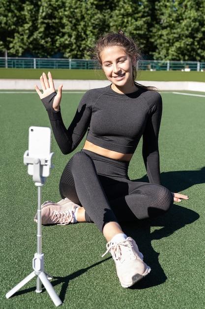 Kobieta W Vlogger Odzieży Sportowej Siedzi Na Zewnątrz Sztucznej Murawy Premium Zdjęcia