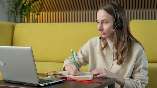 Kobieta W Zestawie Słuchawkowym Siedzi Na żółtej Kanapie W Domu I Rozmowy Wideo Na Komputerze Przenośnym. Premium Zdjęcia