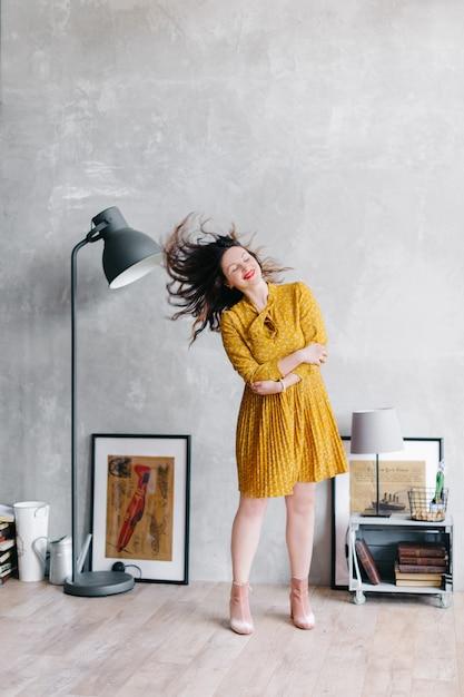 Kobieta W żółtej Sukience Macha Włosami. Dziewczyna Zostaje W Domu I Wariuje Na Punkcie Izolacji, Jej Włosy Lecą. Modny Portret W Stylowym Wnętrzu. Premium Zdjęcia