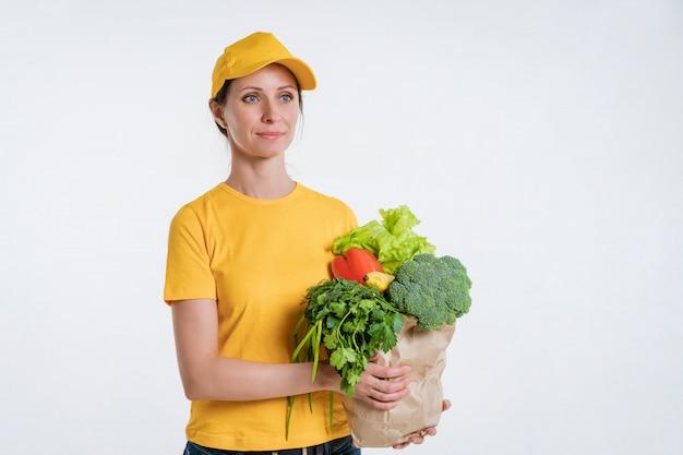 Kobieta W żółtych Ubraniach, Dostarczająca Paczkę Jedzenia, Na Białym Tle Premium Zdjęcia