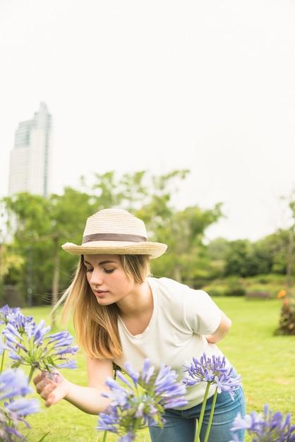 Kobieta Wącha Kwiaty W Ogródzie Darmowe Zdjęcia