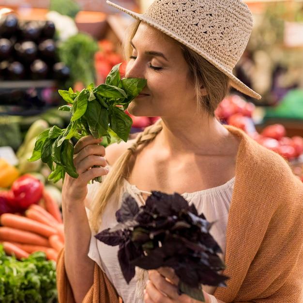 Kobieta Wącha Naturalne Liście Na Rynku Darmowe Zdjęcia