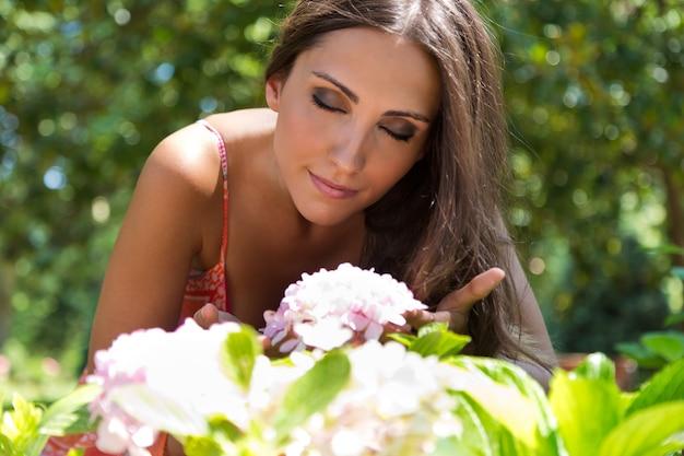Kobieta Wąchania Kwiatów, Siedząc Na Trawie Darmowe Zdjęcia