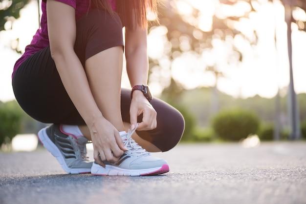 Kobieta wiązanie sznurówki do butów, przygotowuje się do biegania w tle ogród. Premium Zdjęcia