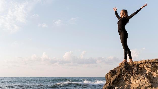 Kobieta Widok Z Boku Z Widokiem Na Wybrzeże Z Miejsca Na Kopię Darmowe Zdjęcia
