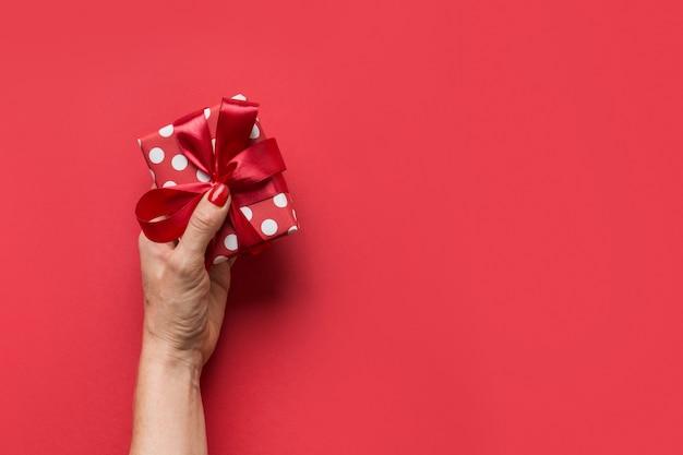 Kobieta Wręcza Mienia Czerwonego Giftbox Z Czerwonym łękiem Na Szarym Tle Premium Zdjęcia