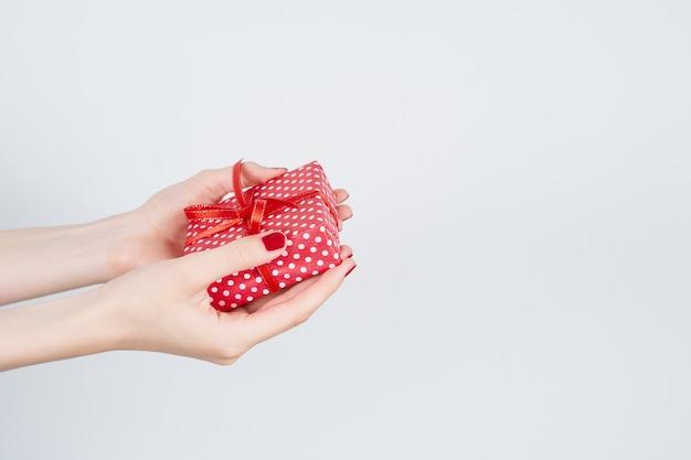 Kobieta Wręcza Mieniu Czerwonego Prezent Z Faborkiem, Robiący Manikiur Ręki Z Gwoździa Połyskiem Na Bielu Premium Zdjęcia