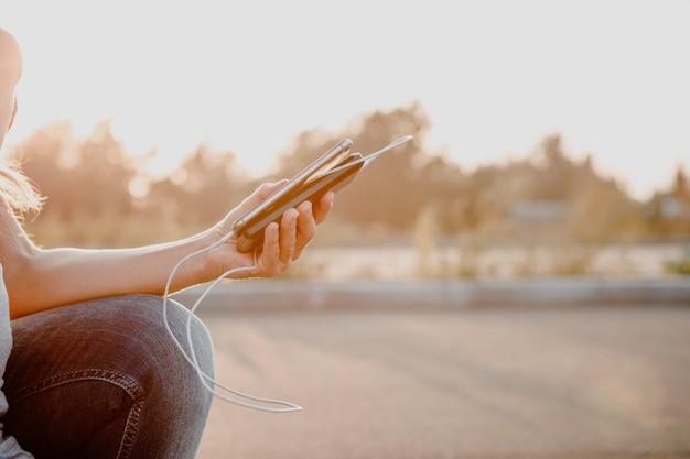 Kobieta wręcza trzymać czarnego smartphone ładuje baterię od zewnętrznego zasilania banka Premium Zdjęcia