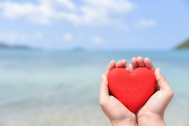 Kobieta Wręcza Trzymać Czerwonego Serce Na Plaży Z Zamazanym Morza I Niebieskiego Nieba Tłem. Koncepcja Miłości. Premium Zdjęcia