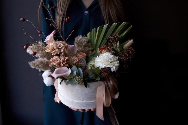 Kobieta wręcza trzymać pudełko z rocznika bukietem na ciemnym tle Premium Zdjęcia