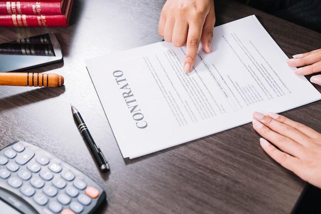 Kobieta wskazuje przy dokumentem blisko damy przy stołem z kalkulatorem, smartphone i piórem ,. Darmowe Zdjęcia
