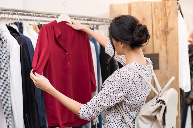 Kobieta Wybiera Bluzkę Z Nowej Kolekcji Ubrań W Butiku Premium Zdjęcia