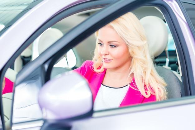 Kobieta wybiera samochód dla kupować w przedstawicielstwie handlowym Premium Zdjęcia