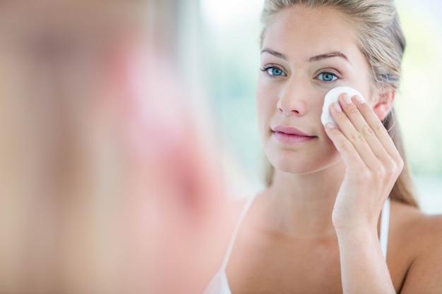 Kobieta wyciera twarz z wacikiem w łazience Premium Zdjęcia