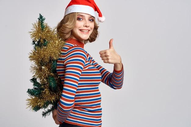 Kobieta Z Choinką W Ręku żółte świecidełko Prezenty Czapka świąteczna Premium Zdjęcia