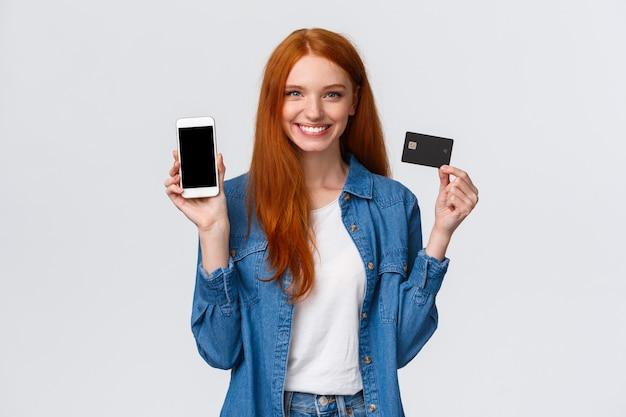Kobieta Z Czerwonymi Długimi Włosami Trzyma Kartę Kredytową I Pokazuje Smartphone Premium Zdjęcia