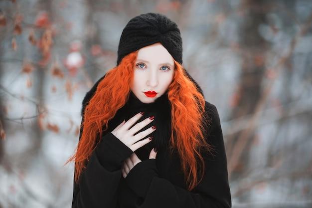Kobieta Z Czerwonymi Włosami W Czarnym Płaszczu Z Futrem Na Tle Zimowego Lasu. Rudowłosa Dziewczyna O Bladej Skórze I Niebieskich Oczach O Jasnym, Niezwykłym Wyglądzie Z Turbanem Na Głowie. Styl Damski Premium Zdjęcia