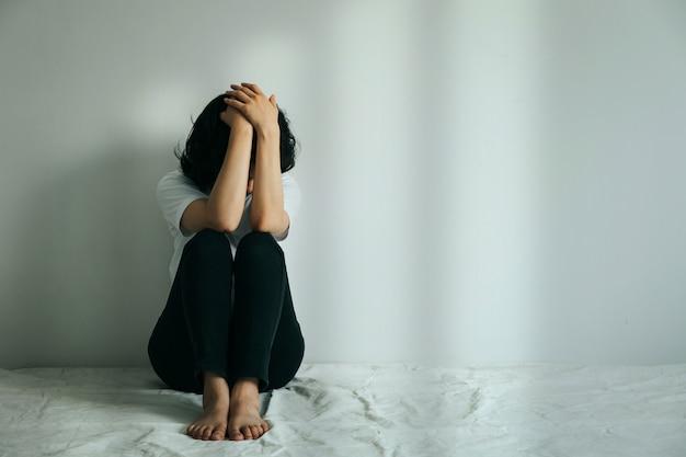 Kobieta Z Depresją ściska Kolano I Płacze. Smutna Kobieta Siedzi Sama W Pustym Pokoju. Premium Zdjęcia