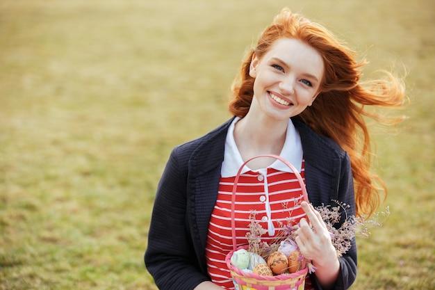 Kobieta Z Długimi Włosami, Trzymając Wielkanocny Kosz Piknikowy Darmowe Zdjęcia