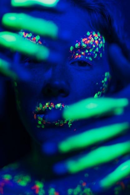 Kobieta Z Fluorescencyjnym Makijażem Na Twarzy I Rękach Darmowe Zdjęcia