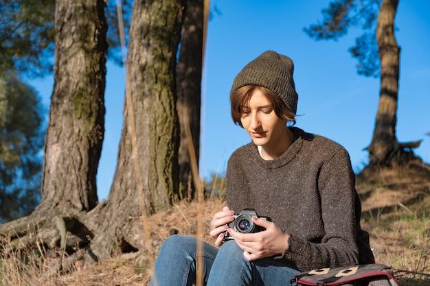 Kobieta Z Kamerą Filmową, Ciesząc Się Piękną Jesienną Pogodą Na świeżym Powietrzu. Młoda Kobieta Turysta Siedzi Pod Sosnami W Słoneczne Popołudnie Premium Zdjęcia
