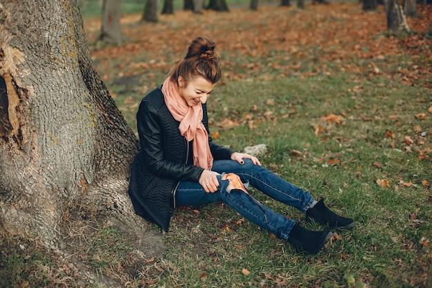 Kobieta Z Kontuzją Nogi. Ranna Dziewczyna Siedząca Przy Drzewie. Rana Krwawi. Darmowe Zdjęcia