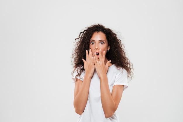 Kobieta Z Kręconymi Włosami Stojący I Obejmujące Usta Rękami Darmowe Zdjęcia