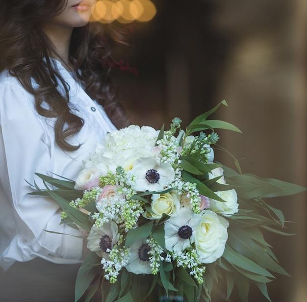Kobieta z kręconymi włosami, trzymając biały bukiet kwiatów. Darmowe Zdjęcia
