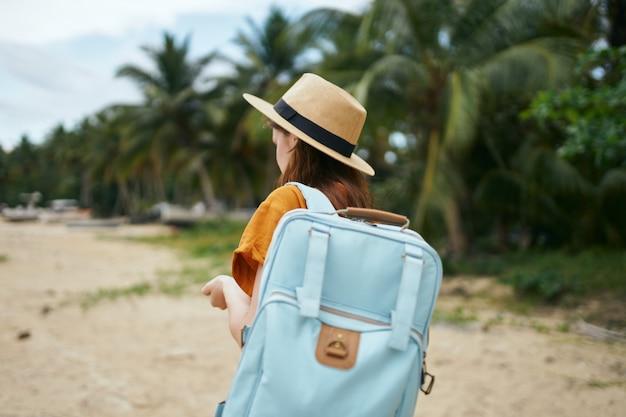 Kobieta Z Niebieskim Plecakiem W żółtej Sukience I Kapeluszu Idzie Oceanem Wzdłuż Piasku Z Palmami Premium Zdjęcia