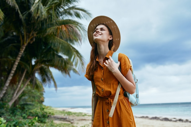 Kobieta Z Niebieskim Plecakiem W żółtej Sukience I Kapeluszu Idzie Wzdłuż Oceanu Wzdłuż Piasku Z Palmami Premium Zdjęcia