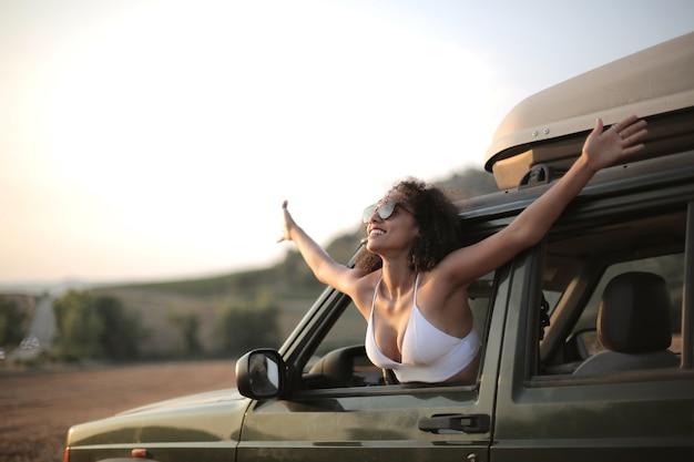 Kobieta Z Otwartymi Rękami, Patrząc Przez Okno Samochodu Darmowe Zdjęcia