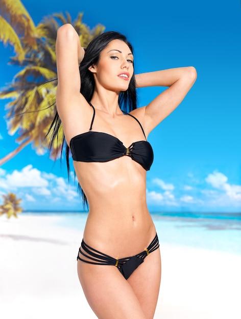 Kobieta Z Pięknym Ciałem W Czarnym Bikini Opalać Się Na Plaży Darmowe Zdjęcia