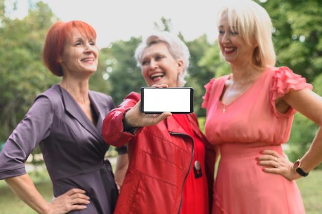 Kobieta z przyjaciółmi posiadającymi telefon komórkowy Darmowe Zdjęcia