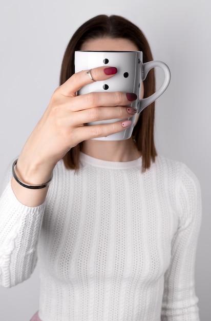 Kobieta Z Różowym Manicure'em W Minimalistycznym Stylu Trzyma Filiżankę Kawy Lub Herbaty Premium Zdjęcia