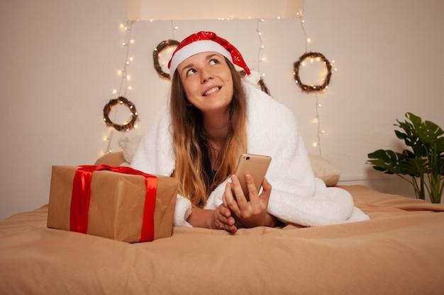 Kobieta Z Santa Hat I Pudełko Na łóżku. Dekoracja świąteczna. Premium Zdjęcia