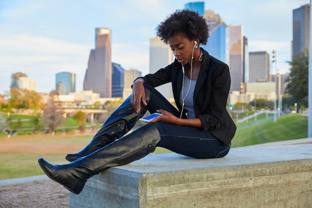 Kobieta Z Smartphone Obsiadaniem W Parku Premium Zdjęcia