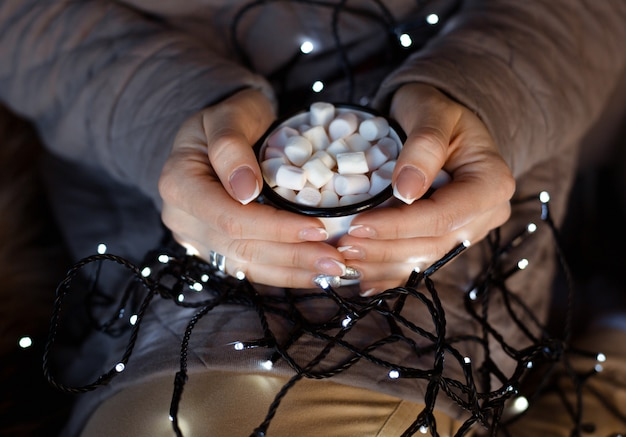 Kobieta z świąteczną girlandą na kolanach ogrzewa ręce na białym tle Premium Zdjęcia