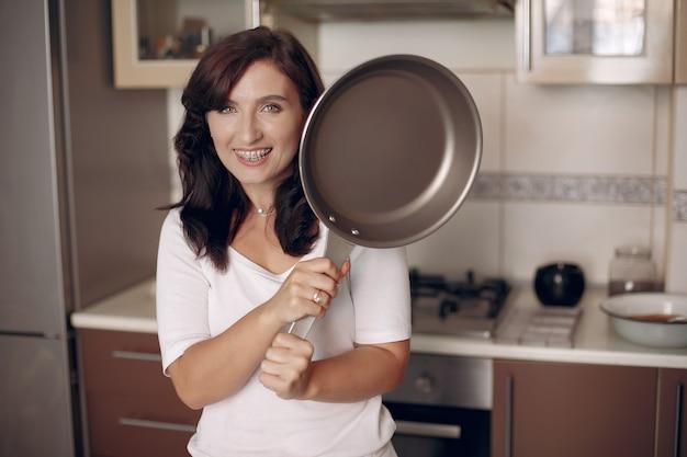 Kobieta Z Szelkami Patrzy W Kamerę I Uśmiecha Się. Pani Przygotowuje Jedzenie. Darmowe Zdjęcia