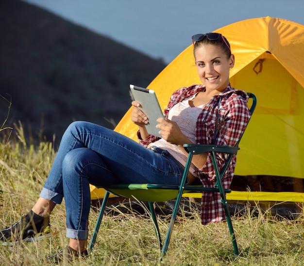 Kobieta Z Tabletem Siedzi W Fotelu. Campingowa Przygoda Premium Zdjęcia