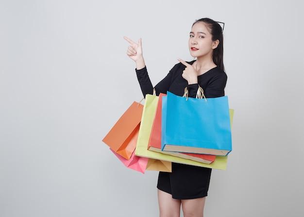 Kobieta Z Torba Na Zakupy Stoi Na Bielu Premium Zdjęcia