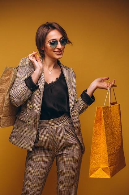 Kobieta Z Torba Na Zakupy W Studiu Na żółtym Tle Odizolowywającym Darmowe Zdjęcia