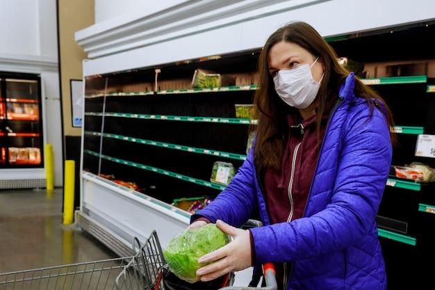 Kobieta Z Twarzy Maską Kupuje Sałaty Przy Supermarketem Z Pustymi Półkami. Premium Zdjęcia