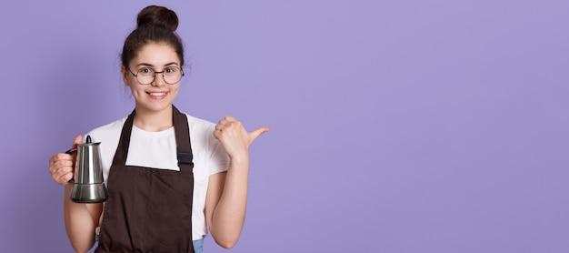 Kobieta Z Uroczym Uśmiechem Na Sobie Okulary, T-shirt I Brązowy Fartuch, Wskazując Na Bok Kciukiem Darmowe Zdjęcia
