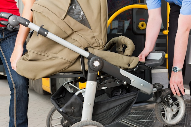 Kobieta z wózkiem wsiada do autobusu Premium Zdjęcia