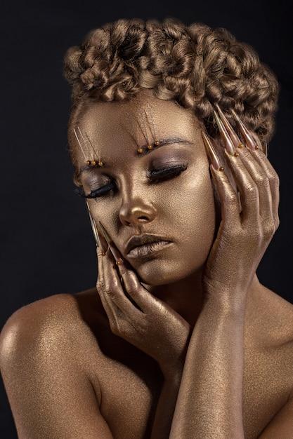 Kobieta z złotym makeup. błyszcząca biżuteria z efektem skóry. Premium Zdjęcia