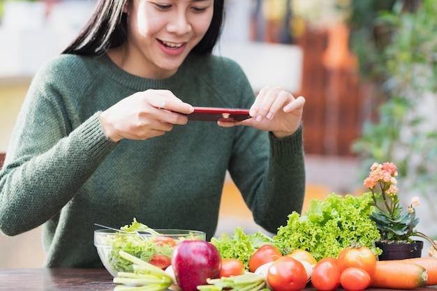 Kobieta Za Pomocą Smartfona Zrób Zdjęcie Zdrowej żywności Przed Jedzeniem. Premium Zdjęcia